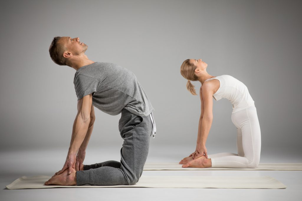 Couple practicing yoga standing in Ushtrasana position or Camel pose