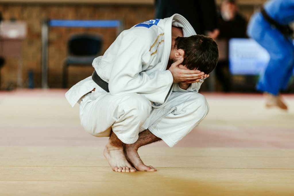 defeat judoka in white kimono is sitting covering face in his hands