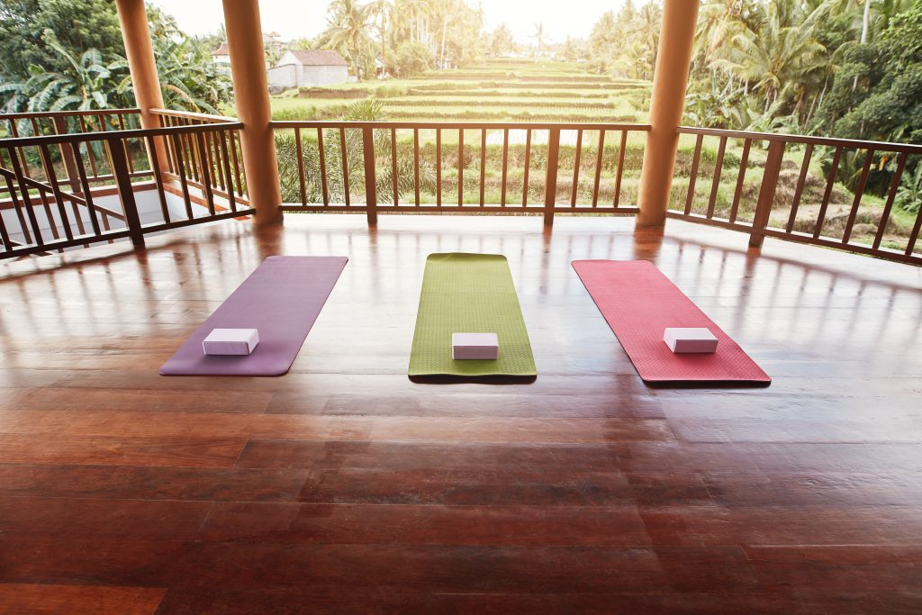 Empty yoga studio with colorful mat and yoga brick.