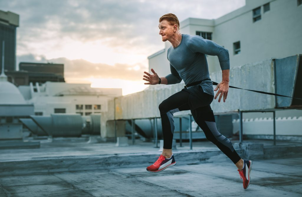 Fitness man running on terrace of a building with a resistance band to his waist. Man doing workout on rooftop doing resistance running.