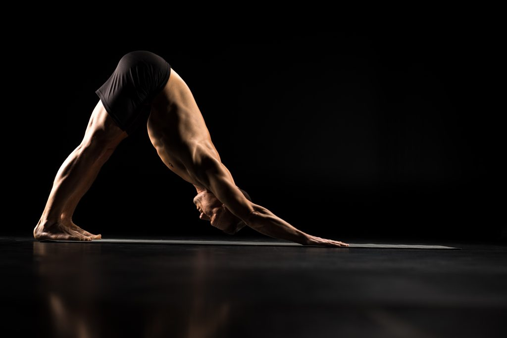 Man performing Adho Mukha Svanasana or Downward Facing Dog Pose