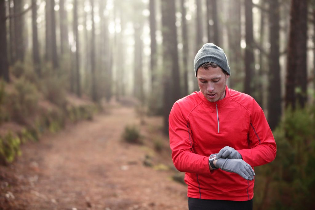 Trail runner man looking at heart rate monitor watch running in cold forest wearing hat and gloves. Male jogger running training in woods.